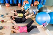 stock photo of crunch  - Fitball crunch training group core fitness at gym abdominal workout - JPG