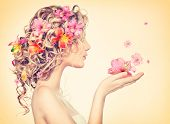 Beauty girl takes beautiful flowers in her hands. Blowing flower. Hairstyle with flowers.  Fantasy girl portrait in pastel colors. Summer fairy portrait. Long permed hair. poster