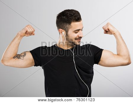 Beautiful latin man listen music and appreciate his own muscles