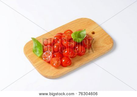 wooden cutting board with halved cherry tomatoes decorated with fresh basil