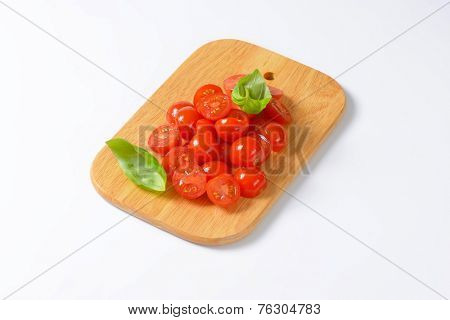 halved cherry tomatoes with basil served on the wooden cutting board