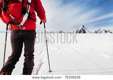 Mountaineer exploring a glacier with the skis during a high-altitude winter expedition in the european Alps. In background the Matterhorn, Zermatt, Switzerland, Europe.