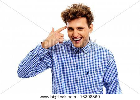 Portrait of a funny young man pointing finger gun gesture to head