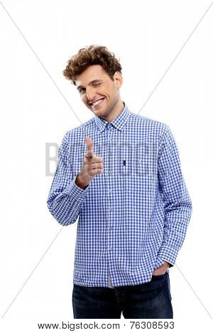 Smiling young man pointing at camera over white background