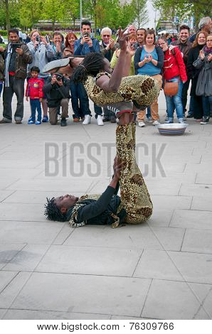 LONDON - 09 JUNE 2013: Group of Jamaican street performers and acrobats giving a performance for a group of people at Southbank, London, England on 09 June 2013