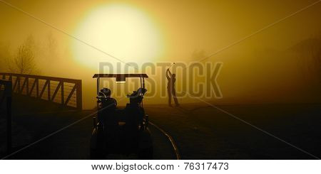 Golfer in the Golden Sunrise fog on a misty morning with a golf cart