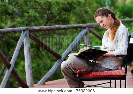 Young woman on safari vacation reading on balcony with breathtaking views of savannah
