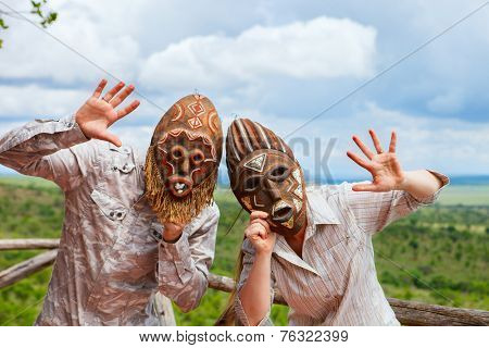 African vacation. Happy couple in african masks at balcony in safari lodge.