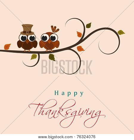 Cute little birds with pilgrim hat sitting on a maple tree branch on beige background for Happy Thanksgiving Day celebrations.