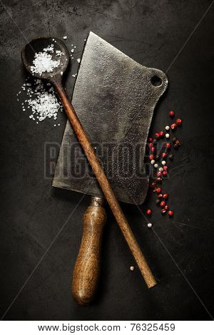old wooden spoon and Meat cleaver knife on dark background