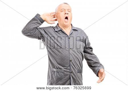 Sleepy senior in pajamas stretching on white background