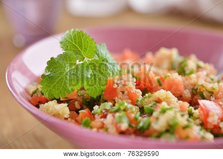 Tabbouleh with quinoa, tomato, chives, and mint. Selective focus on the mint leaf