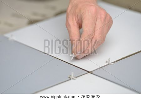 Construction worker set up spacers between tiles on a floor