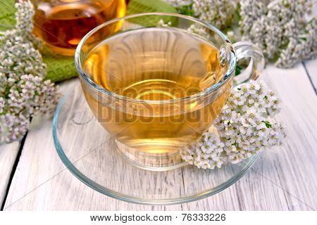 Tea with yarrow in glass cup on light board