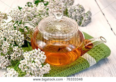 Tea with yarrow in glass teapot on napkin