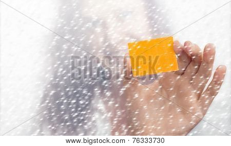 Girl's Hand With A Yellow Slip Of Paper In The Snowfall