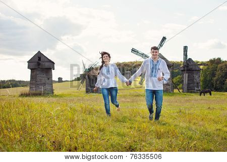 Happy young couple running on the field