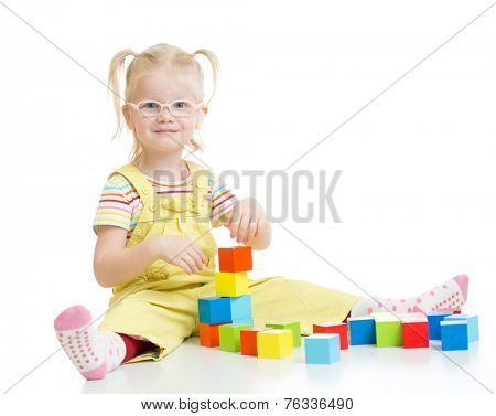 Funny kid in eyeglases making tower using blocks isolated on white