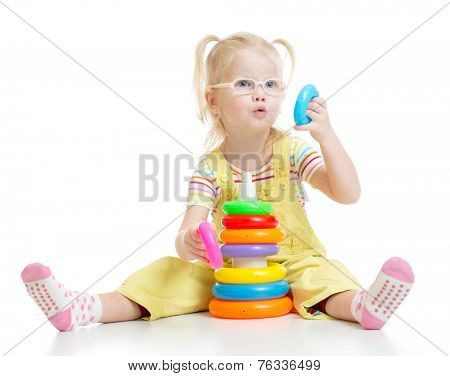 Funny kid in eyeglases playing colorful pyramid toy isolated on white
