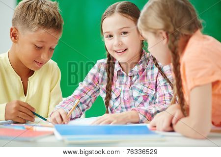 Cute learner looking at camera at lesson of drawing with her classmates near by