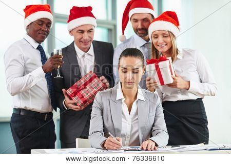 Portrait of serious female employee analyzing document with group of colleagues preparing her Christmas surprise
