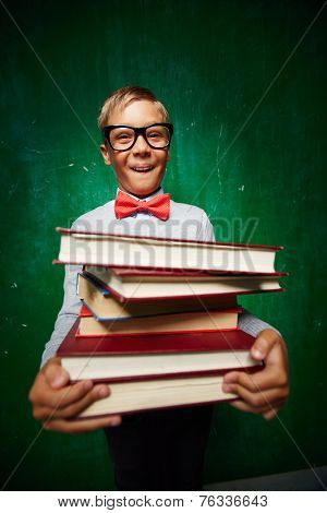 Ecstatic kid in eyeglasses and smart casual holding pile of books