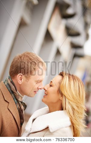 Amorous man going to kiss romantic woman