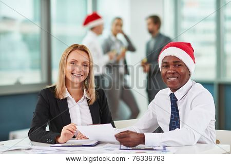 Portrait of joyful colleagues looking at camera at workplace on background of their business partners