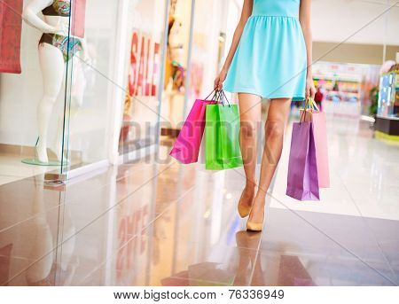Legs of attractive shopaholic in blue dress walking down mall