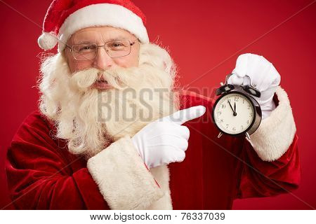 Smiling Santa pointing at alarm clock in his hand showing five minutes to twelve
