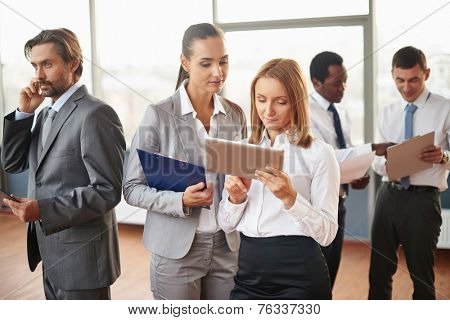 Two female employees using touchpad with several co-workers doing their job near by