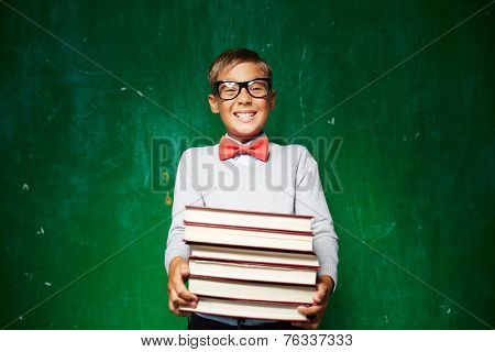 Happy schoolboy in smart casual holding stack of books