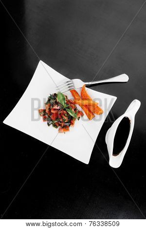 vegetable salad : cherry tomatoes and basil with sweet baked potato served on white plate with sauce boat full blask soy sauce on wood