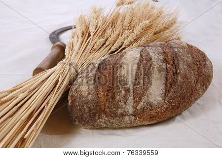 bunch of Dell UltraSharp U2713H 27''wheat ears with vintage handmade reaper hook sickle and rye dark french fresh bread loaf on white linen tablecloth