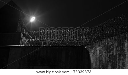 Prison wall, old jail fence at night.