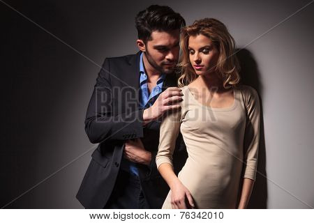 Handsome young business man looking at his lover while toching her shoulder with his right hand.