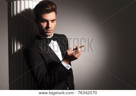 Picture of a elegant business man leaning on a column while looking at the camera with a cigarette in his right hand.