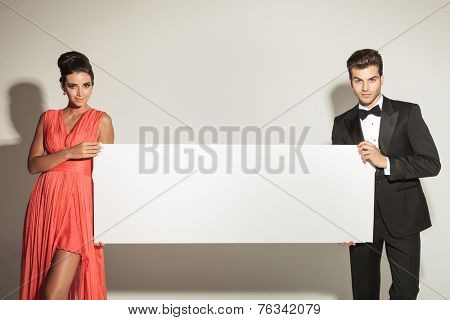 Fashion man and woman looking at the camera while holding a blank board.