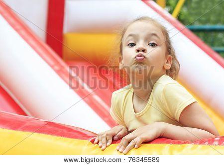 Joyful little girl makes a face on trampoline.