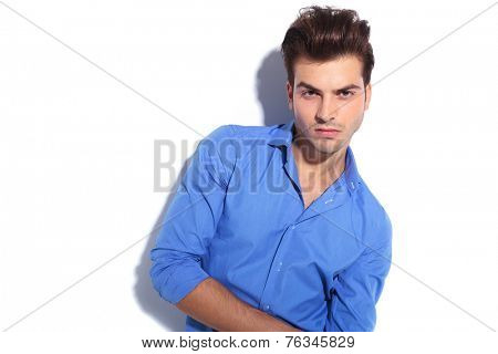 Close up picture of a handsome young man leaning on a white wall, looking at the camera.