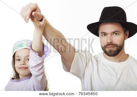 Man in Jewish hat and girl in skullcap.