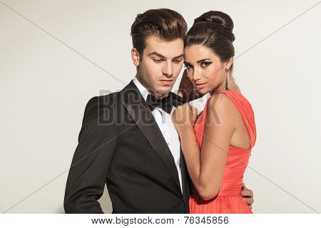 Close up picture of a young elegant couple embracing, the man is looking down while the woman is looking at the camera.