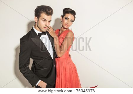 Beautiful young fashion woman embracing her lover while he is holding one hand in pocket, looking down.