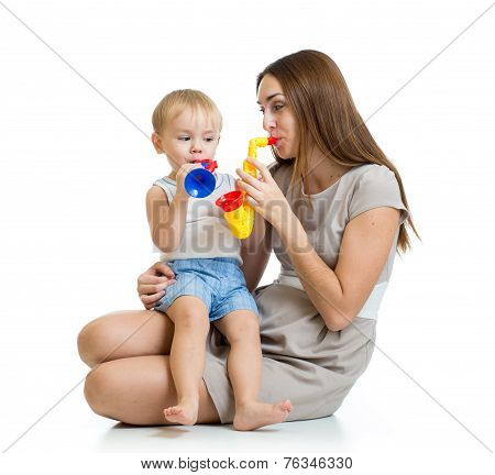 child and mother play musical toys isolated