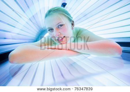 Pretty, young woman tanning her skin in a modern solarium/sunbed