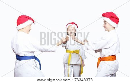 Athletes in caps of Santa Claus girl is judging a fight between two boys