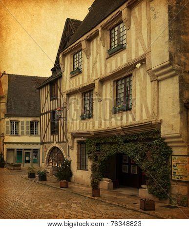 Old houses on  Place de l'hotel de ville,   Noyers-sur-Serein, Yonne, Burgundy, FRANCE.  Photo in retro style. Paper texture.