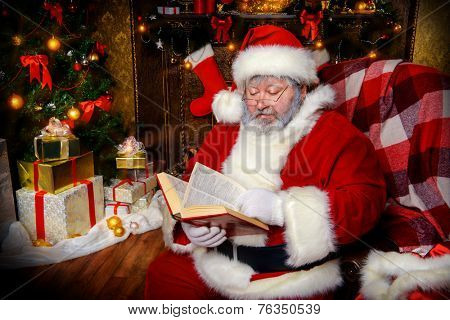 Santa Claus sat down to rest by the fireplace and to read a book. Home decoration.