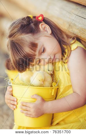 Happy little girl playing with chickens outdoors