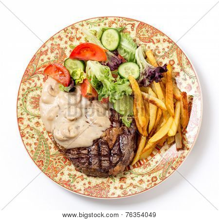 Bird's eye view of grilled rib-eye beef steak served with mushroom sauce, salad and potato chips.